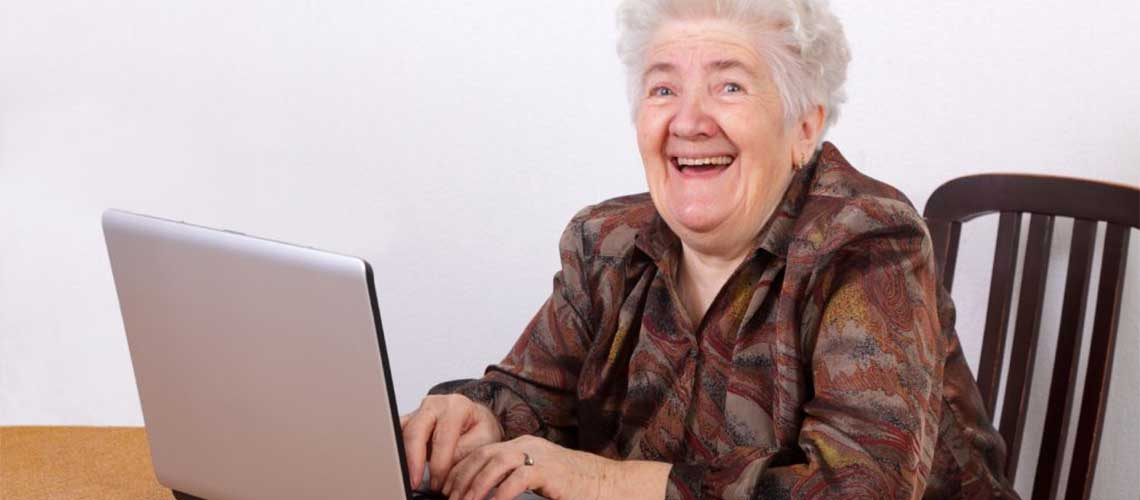 Older lady smiling and using a laptop