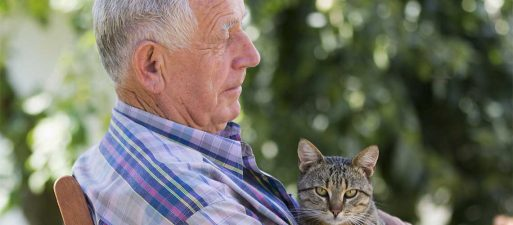 Older retired man holding cat