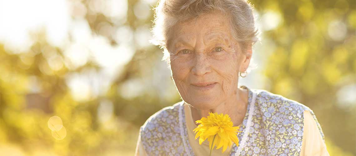Older lady holding flower on sunny day