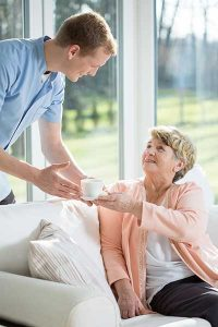 Carer handing an elderly woman a cup of tea