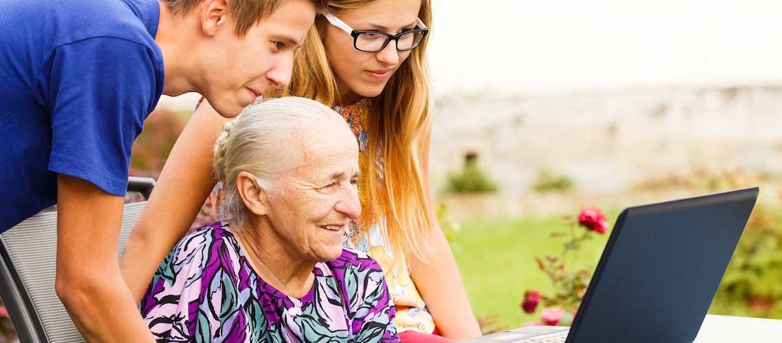 Elderly lady on laptop with grandchildren