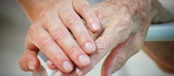 Young hand holding elderly hand