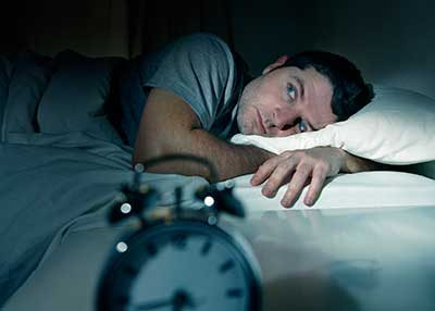 Man laying awake worrying in bed